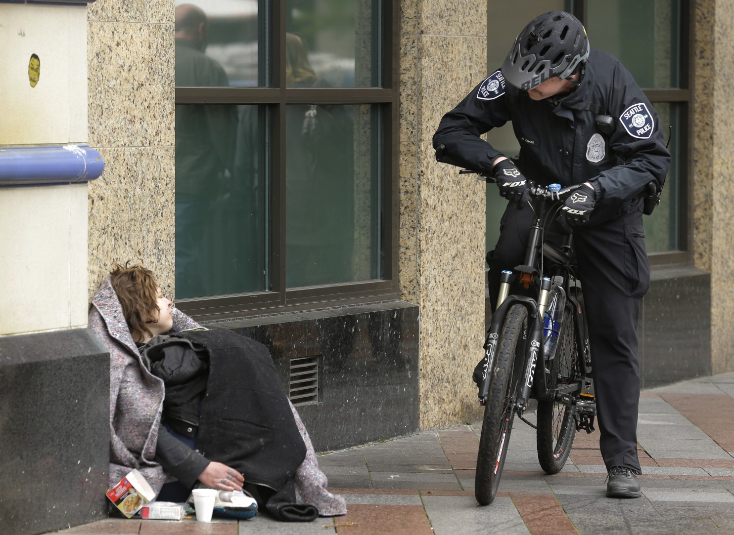 a police officer speaks with a person resting on the street